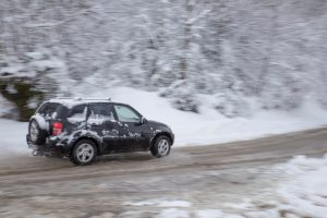 Ponga, Spain - February 27, 2016: Toyota SUV driving after a heavy a snowfall with snow and water on the roads